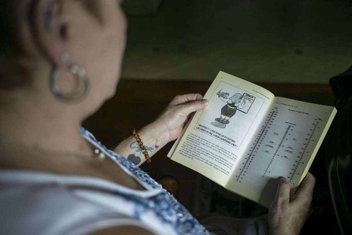 """Laurie Nelson looks through her copy of """"The Liver Cleansing Diet"""" by Dr. Sandra Cabot, at her home in Cibolo on Aug. 10, 2018. Nelson recently learned she no longer has nonalcoholic steatohepatitis, or NASH, after 19 years of having the disease. She credits the book, research she did online and bariatric surgery, which helped her lose weight."""
