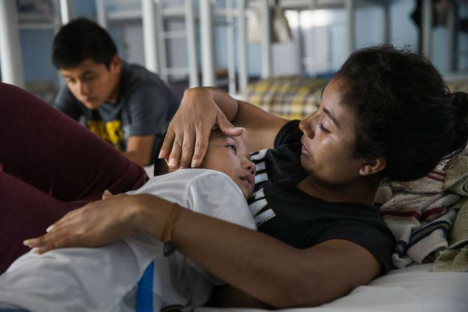 In a Wednesday, June 20, 2018 photo, families, who are waiting to cross the border seek shelter at Senda De Vida Casa Del Emigrante, in the border town of Reynosa, Mexico. Patricia Flores, 27, consoles her son, Joan, 7, in the centers dormitory. Patrica said her family, who made the journey from El Salvador, are hesitant to attempt to seek asylum for fear of US immigration policies. (Amanda Voisard/Austin American-Statesman via AP) Photo: Amanda Voisard, Associated Press