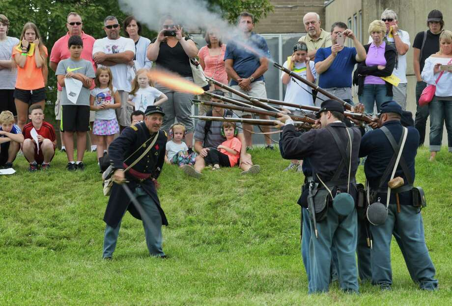 Visitors watch from a hill as re-enactors portraying Union soldiers fire their muskets during an infantry drill during the Civil War Weekend put on by the Friends of Grant Cottage on Sunday, Aug. 12, 2018, in Wilton, N.Y. All funds raised from the weekend event will be used in the preservation of Grant Cottage.  (Paul Buckowski/Times Union) Photo: Paul Buckowski / (Paul Buckowski/Times Union)