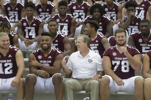 Texas A&M football coach Jimbo Fisher laughs with players as they gather for a team photo at Kyle Field on Sunday in College Station.