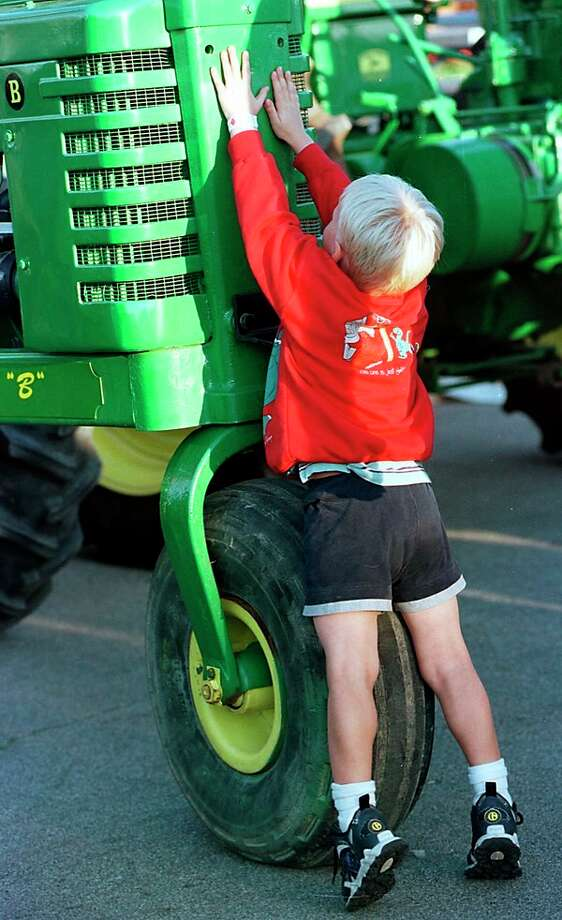 Four-year-old Andrew Wylie checks out a John Deere tractor at the Midland County Fair in this 1998 Daily News file photo.