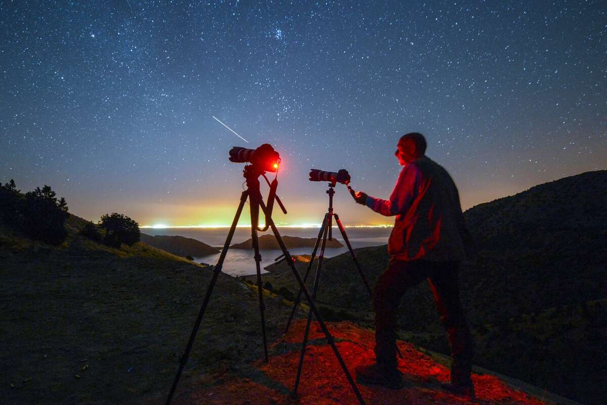 VAN, TURKEY - AUGUST 13: A photographer stands near a set-up as a Perseid meteor, also known as