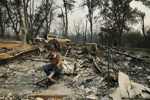 Kim Burns sits in the charred rubble of her home burned in the Carr Fire, Sunday, Aug. 12, 2018, in Redding, Calif. (AP Photo/John Locher)