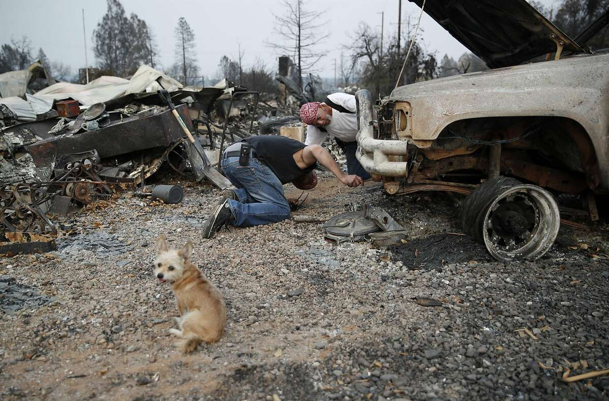 Frank Arellano, right, and T.J. Pilkington look under a car burned in the Carr Fire, Friday, Aug. 10, 2018, in Redding, Calif. (AP Photo/John Locher)