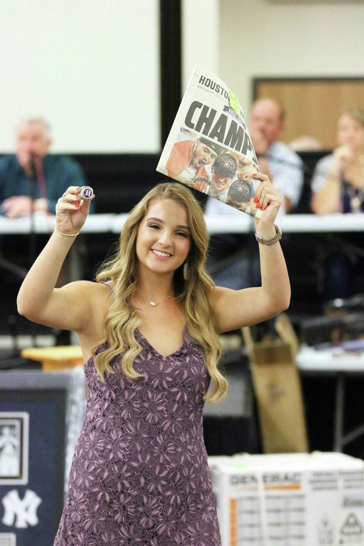 Aly Sjolander holds one of the Houston Astros World Champions replica rings and a souvenir copy of the Houston Chronicle?'s CHAMPS newspapers above her head as she shows them off during the live auction at the Liberty-Dayton Chamber of Commerce?'s 500 fundraiser Friday night.