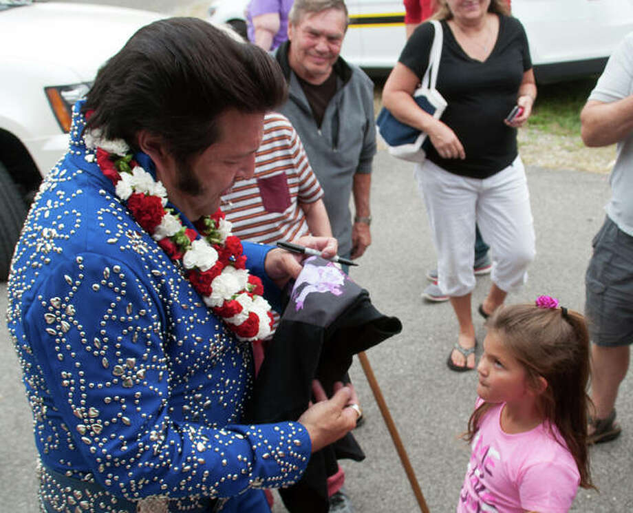 An Elvis Presley impersonator enchants a young fan during last year's fall festival in Benld.