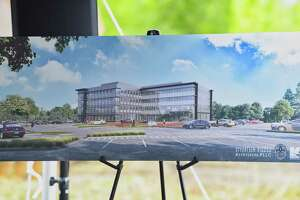 An artist's rendition of what the new Ayco headquarters will look like is seen on display during a groundbreaking ceremony for the building at the site of the former Starlite theater and Colonie Coliseum on Monday, Aug. 13, 2018, in Colonie, N.Y.   (Paul Buckowski/Times Union)
