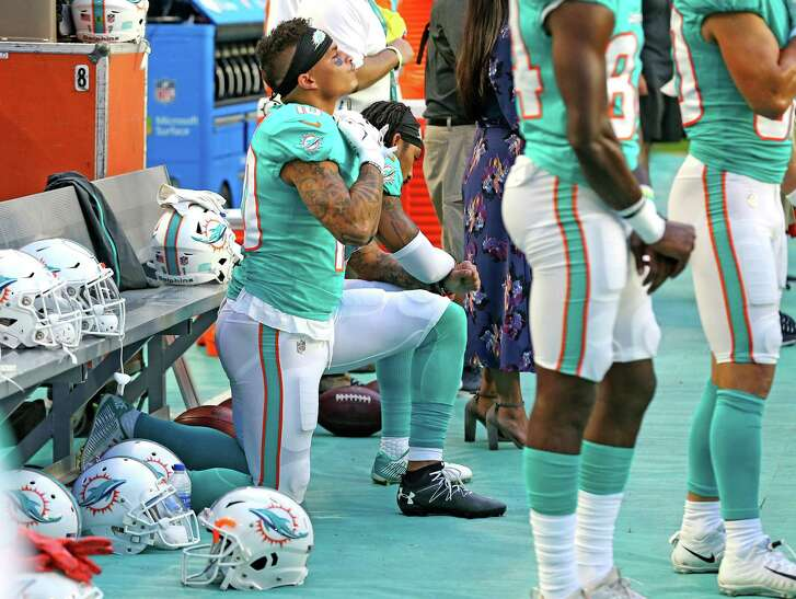 Miami Dolphins receivers Kenny Stills and Albert Wilson kneel during the national anthem as they prepare to play the Tampa Bay Buccaneers at Hard Rock Stadium in Miami Gardens, Fla., on Thursday, Aug. 9, 2018. (Charles Trainor Jr./Miami Herald/TNS)