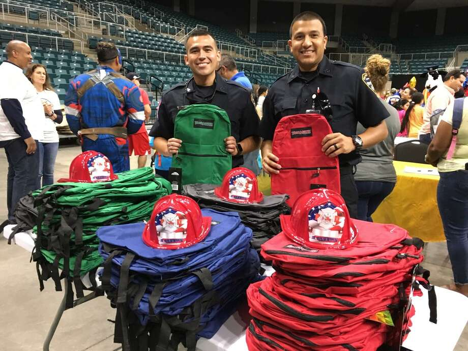 Helping to make sure that youngsters have a good start to the school year were Katy Fire Department firefighters and EMTs Enrique Escobedo and Julio Garcia. In addition to picking their favorite backpack, youths also could choose a fire helmet. Photo: Karen Zurawski / Karen Zurawski