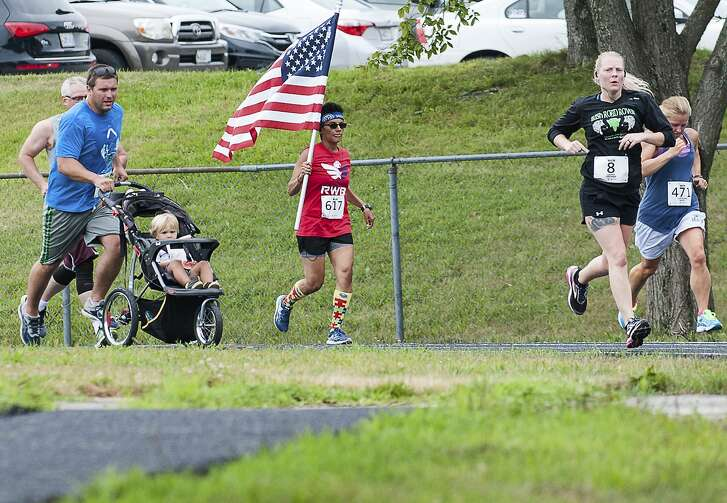 Sarah Greaney, of Lewiston, Maine carries the American flag Sunday July 22, 2018, as she heads into the home stretch of Emily's Run that started and finished at Edward Little High School in Auburn, Maine. She has no military background but is a member of Team Red White and Blue, a national service organization that brings physical fitness challenges and fun social activities to veterans combating PTSD. The race, in it's 14th year is run in honor of Emily Fletcher, a local runner killed in an automobile accident in 2004. (Russ Dillingham/Sun Journal via AP)