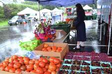 Alexandra Koletsos of Gazy Bros. Farm in Oxford gets things ready in the rain for the start of the sale at the weekly New Canaan Farmers' Market, Saturday, Aug. 11, 2018, in New Canaan, Conn.