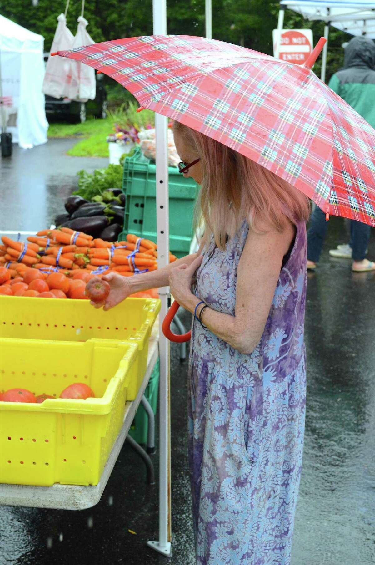 Eve Martin of Darien checks out some tomatoes at the weekly New Canaan Farmers' Market, Saturday, Aug. 11, 2018, in New Canaan, Conn.