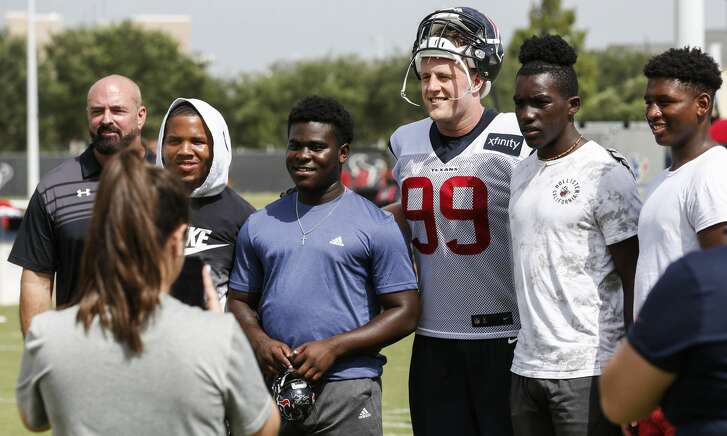 Houston Texans defensive end J.J. Watt (99) stops to take a photo with C.E. King football players Joshua Wyatt, Rodrick Crumedy, Jessie Evans and Joshua Wyatt, who visited training camp at the Methodist Training Center on Monday, Aug. 13, 2018, in Houston. The Texans donated last season's field turf to the school, after their stadium was flooded in the aftermath of Hurricane Harvey.