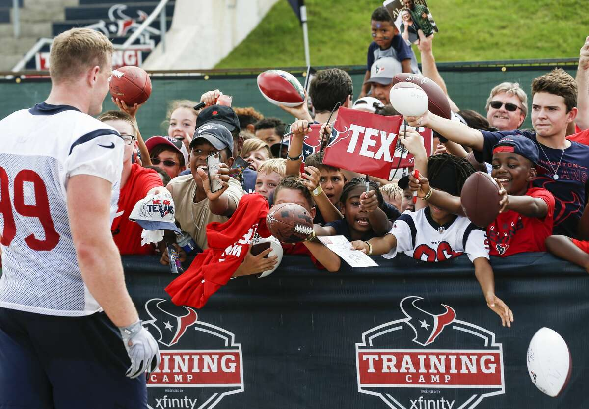 Houston Texans defensive end J.J. Watt (99) walks up to a group of fans to sign autographs during training camp at the Methodist Training Center on Monday, Aug. 13, 2018, in Houston.