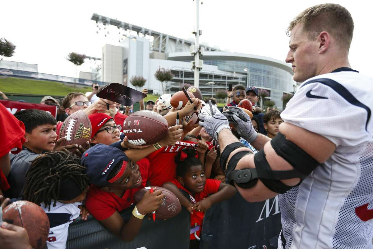 Houston Texans defensive end J.J. Watt signs autographs during training camp at the Methodist Training Center on Monday, Aug. 13, 2018, in Houston.