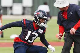 Houston Texans wide receiver Braxton Miller (13) runs a pass route past wide receivers coach John Perry during training camp at the Methodist Training Center on Monday, Aug. 13, 2018, in Houston.