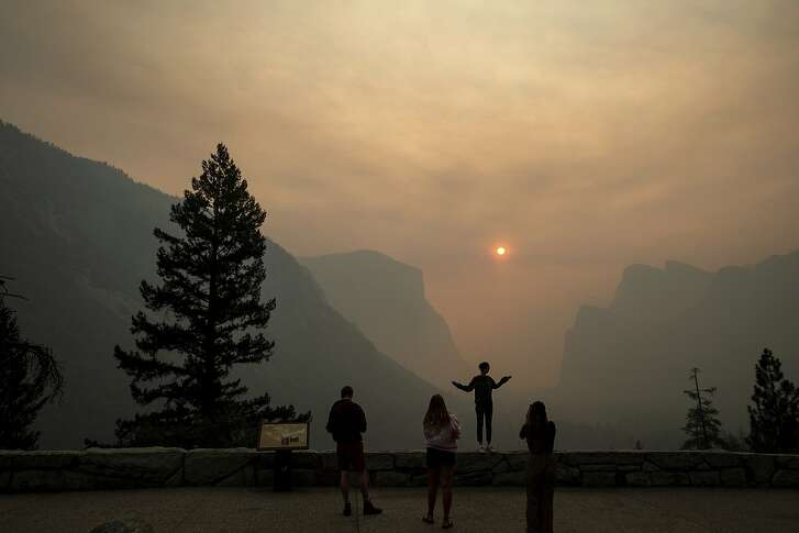 FILE - In this July 25, 2018 file photo, Hannah Whyatt poses for a friend's photo as smoke from the Ferguson Fire fills Yosemite Valley in Yosemite National Park, Calif. Yosemite National Park will reopen Tuesday, Aug. 14, 2018, 14 days after a wildfire choked the park with smoke at the peak of tourist season. Park spokesman Scott Gediman said Friday, Aug. 10, visitors should expect limited hours and visitor services as the park returns to normal. The scenic Yosemite Valley and other areas have been closed since July 25 along with hundreds of campsites and hotels. Though the blaze didn't reach the heart of the valley, it burned in remote areas of the park about 250 miles (400 kilometers) from San Francisco, making roads inaccessible and polluting the air with smoke.  (AP Photo/Noah Berger, File)