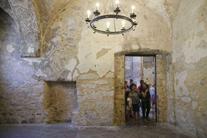 Tourists look into the closed off Sacristy at the Alamo, Tuesday, August 7, 2018. An accumulation of dust due to deterioration is seen along the edges of the wall and floor.