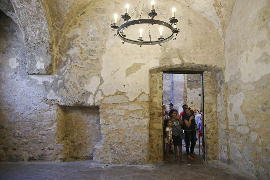 Tourists look into the closed off Sacristy at the Alamo, Tuesday, August 7, 2018. An accumulation of dust due to deterioration is seen along the edges of the wall and floor. Photo: JERRY LARA/San Antonio Express-News