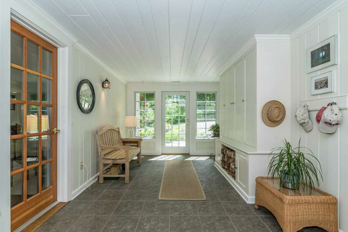 The heated and air conditioned breezeway there is built-in cabinetry, a firewood storage cubby, a door to the front yard, and sliding doors to the deck.