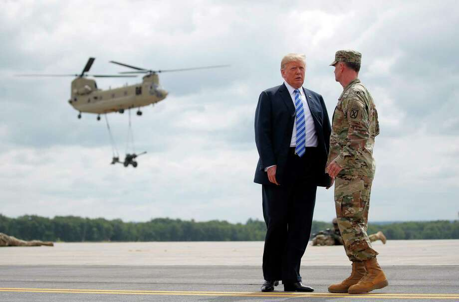President Donald Trump talks with Maj. Gen. Walter Piatt as they watch an air assault exercise at Wheeler-Sack Army Air Field in Fort Drum, N.Y., Monday, Aug. 13, 2018, Photo: Carolyn Kaster, AP / Copyright 2018 The Associated Press. All rights reserved.