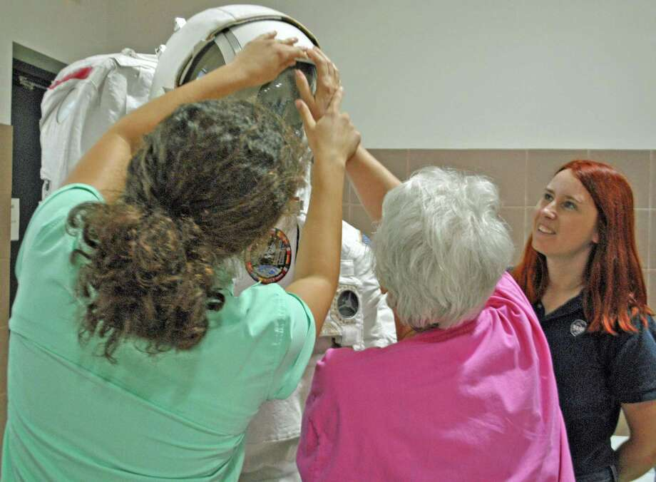 Lighthouse client Becky Sarver (center) learns what a spacesuit looks like with the help of Rice volunteers Mary Pineclo (left) and Tanya Rogers (right). Photo: Courtesy Photo