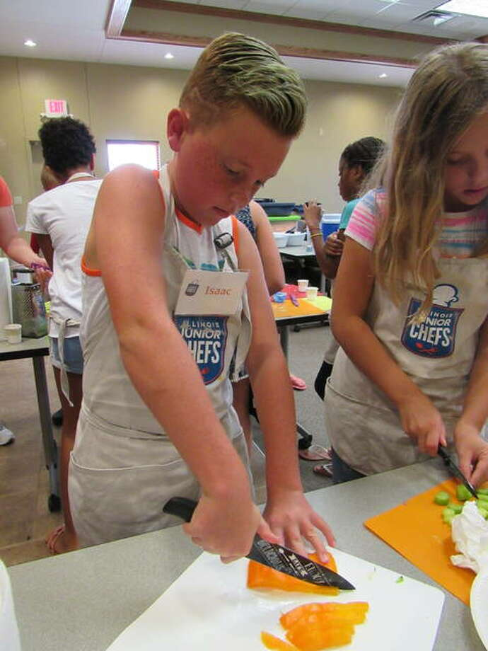 Jr. Chef Isaac Fuhler chops up a bell pepper for the Veggie Chow Mein recipe at the Illinois Jr. Chef Camp in Jerseyville. Photo:       For The Telegraph