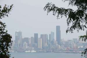 Wildfire smoke from British Columbia causes a haze over the Seattle skyline, Monday, Aug. 13, 2018. More haze, from Washington and California fires, is expected this week as wind patterns shift.