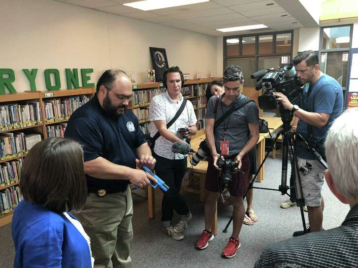 Prospective marshals use Glock 17s, a semiautomatic pistol modified to shoot rubber bullets, in their training on August 10, 2018 at a school in the Pflugerville district. Pictured is Michael Antu, deputy chief and director of enforcement and special services at the Texas Commission on Law Enforcement, as he demonstrates how to load the weapon.