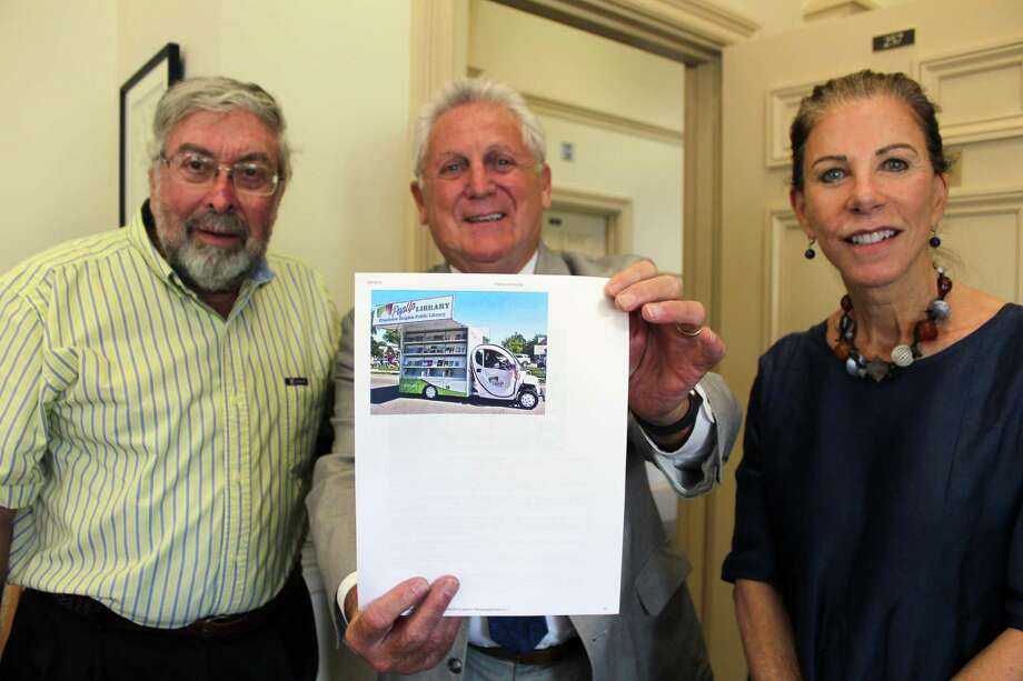 Library Board President Alex Knopp, Mayor Harry Rilling and Library Director Christine Bradley hold up a picture of a bookmobile manufactured by All a Cart in Ohio, the same company they hope will make Norwalk Public Library a similar bookmobile if a special capital appropriation request for $75,000 goes through. Photo: R.A. Schuetz