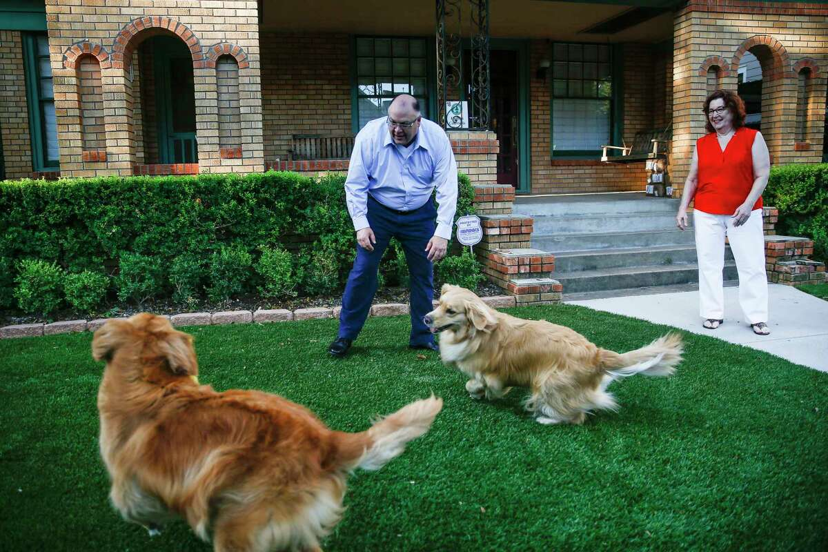 Randall and Etna Neighbour play with their dogs on their new artificial turf lawn Wednesday Aug. 8, 2018 in Houston.