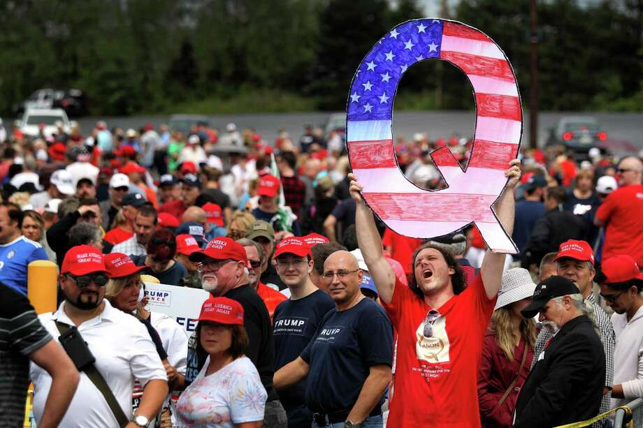 "David Reinert holds up a large ""Q"" sign while waiting in line to see President Donald J. Trump at his rally Aug. 2 in Wilkes Barre, Pennsylvania. ""Q"" represents QAnon, a conspiracy theory group that has been seen at recent rallies. Photo: Rick Loomis / Getty Images / 2018 Getty Images"