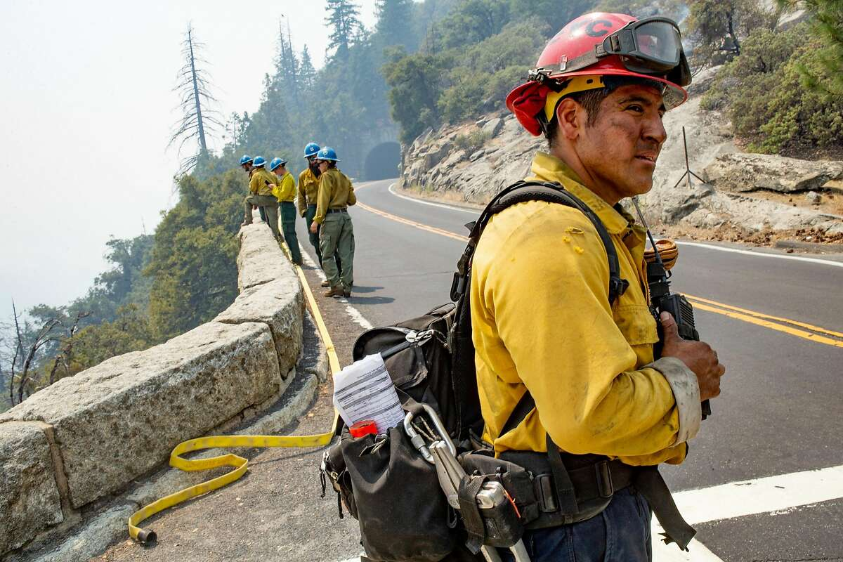 San Diego firefighter Juan Mendez takes a moment to listen to the radio calls near Tunnel View during the Ferguson Fire at National Yosemite Park on Wednesday, Aug. 8, 2018, in Mariposa County, Calif.
