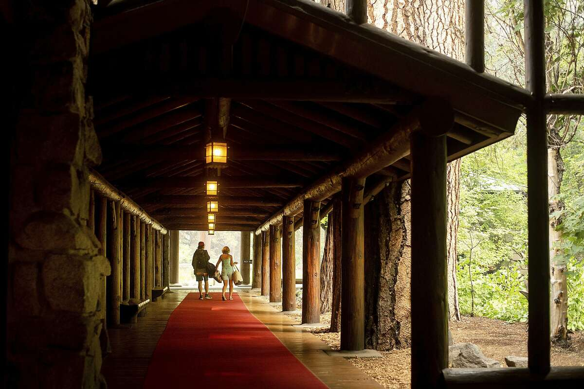 FILE - In this July 25, 2018 file photo, guests leave the The Majestic Yosemite Hotel?, formerly The Ahwahnee Hotel, shortly after it closed in Yosemite National Park, Calif. Yosemite National Park will reopen Tuesday, Aug. 14, 2018, 14 days after a wildfire choked the park with smoke at the peak of tourist season. Park spokesman Scott Gediman said Friday, Aug. 10, visitors should expect limited hours and visitor services as the park returns to normal. The scenic Yosemite Valley and other areas have been closed since July 25 along with hundreds of campsites and hotels. Though the blaze didn't reach the heart of the valley, it burned in remote areas of the park about 250 miles (400 kilometers) from San Francisco, making roads inaccessible and polluting the air with smoke. (AP Photo/Noah Berger, File)