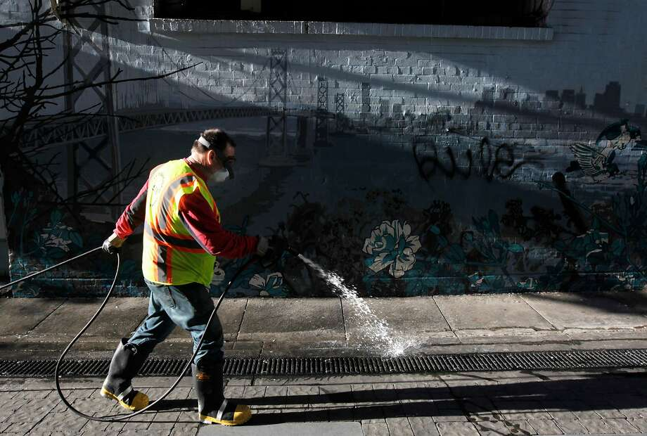 Steve Mahoney sprays disinfectant on the ground before using a power washer to clean Jack Kerouac Alley for the Department of Public Works in San Francisco, Calif. on Wednesday, May 14, 2014. Supervisor Scott Weiner is seeking to boost the department's budget and add additional cleaning crews to battle a growing problem of urine and feces covering streets and sidewalks throughout the city. Photo: Paul Chinn, The Chronicle
