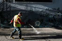 Steve Mahoney sprays disinfectant on the ground before using a power washer to clean Jack Kerouac Alley for the Department of Public Works in San Francisco, Calif. on Wednesday, May 14, 2014. Supervisor Scott Weiner is seeking to boost the department's budget and add additional cleaning crews to battle a growing problem of urine and feces covering streets and sidewalks throughout the city.