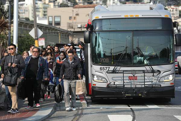 Commuters coming off the L Taravel bus head into the Castro station on Thursday, Aug. 9, 2018 in San Francisco, Calif. Commuters heading in from the western neighborhoods get off the shuttle buses that are looping around the Twin Peaks Tunnel which is closed for repairs.