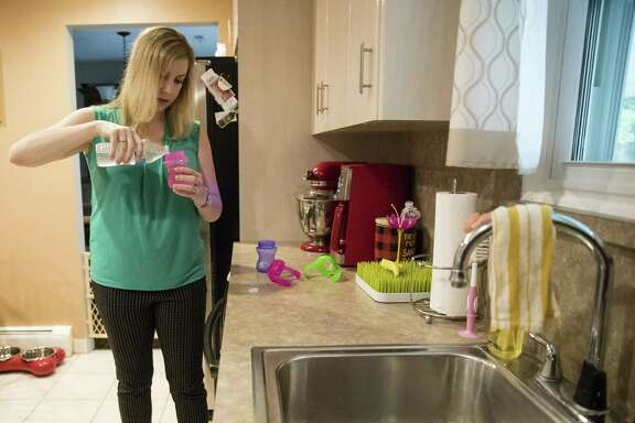 In this Aug. 1, 2018 photo, Lauren Woehr pours bottled water into her 16-month-old daughter Caroline's cup at their home in Horsham, Pa. In Horsham and surrounding towns in eastern Pennsylvania, and at other sites around the United States, the foams once used routinely in firefighting training at military bases contained per-and polyfluoroalkyl substances, or PFAS. EPA testing between 2013 and 2015 found significant amounts of PFAS in public water supplies in 33 U.S. states.