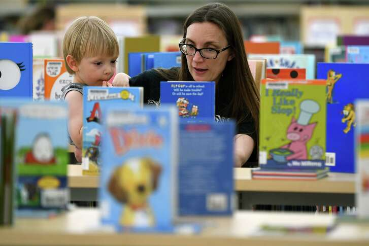 Vanessa Riley, right, and her son Alexander, 3, check out the books in the Children's Library at Barbara Bush Library on May 14, 2018. (Jerry Baker/For the Chronicle)