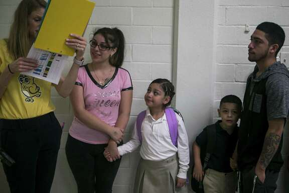 Principal Virginia Silva helps the Angels family, mom Sabrina, Vanitee, 7, Ezekiel, 5, and dad Philipe, find their children's classrooms on the first day of class in 2018 at Democracy Prep at the former Stewart Elementary School campus. The school is run by the New York-based Democracy Prep charter network. The SAISD board will consider an array of partnerships for 18 other schools at its Monday meeting.