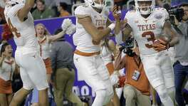 Texas Longhorns wide receivers Lorenzo Joe (14) and Collin Johnson (9) celebrate Texas Longhorns wide receiver Armanti Foreman (3) touchdown in the fourth quarter during the Texas Bowl against Missouri at NRG Stadium on Dec. 27 in Houston. Texas won the game 33-16.