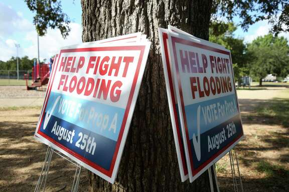 Signs are carried out to rally for Proposition A in the upcoming Harris County Flood Control District Bond Election before a press conference by Harris County leaders, including Houston Mayor Sylvester Turner, Harris County Judge Ed Emmett and Harris County Commissioner Rodney Ellis, on the banks of White Oak Bayou at TC Jester Park on Thursday, Aug. 9, 2018, in Houston. The leaders ask county residents to vote for the $2.5 billion bond proposal to help finance a 10- to 15-year program of flood mitigation projects.