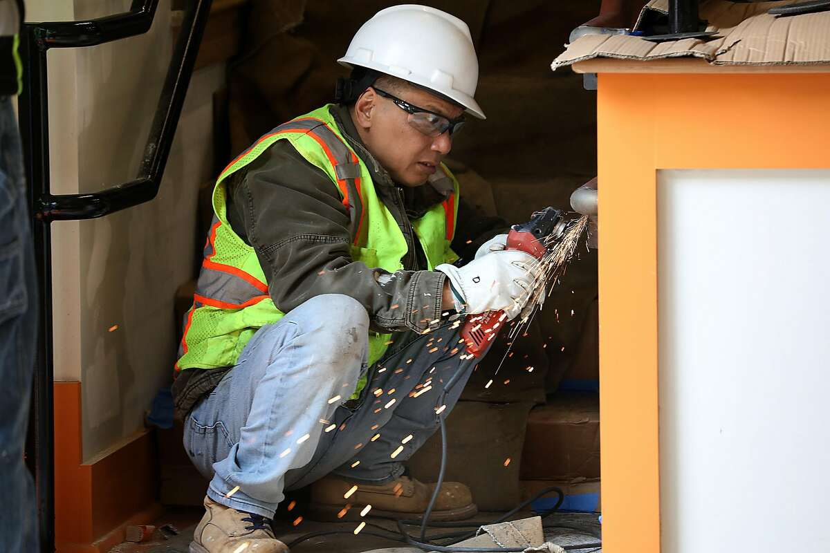 J.Y. Wen welds a hand rail in the auditorium at Redding Elementary school on Monday, Aug. 13, 2018 in San Francisco, Calif. The school has moved forward with construction and hopes to get reimbursed.