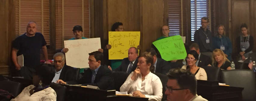 Dozens of employees with Genpak, a food packaging manufacturer in Orange County, lined legislative chambers dressed in green shirts sporting the company's logo and holding signs stating