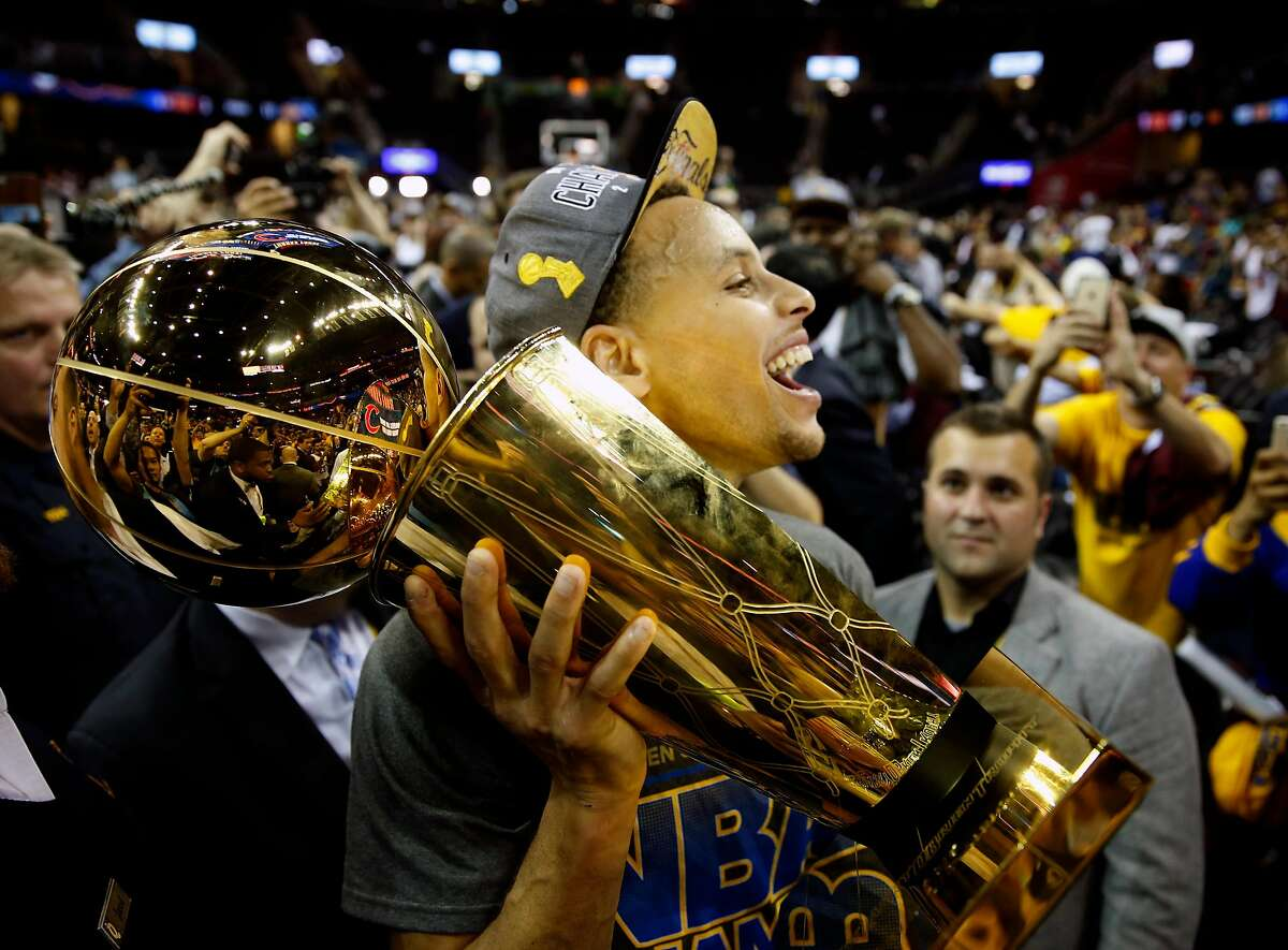Golden State Warriors' Stephen Curry carries the Larry O'Brien Trophy off the court after defeating Cleveland Cavaliers in Game 6 of NBA Finals at Quicken Loans Arena in Cleveland, Ohio, on Tuesday, June 16, 2015.
