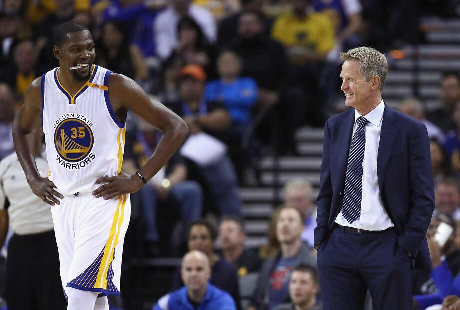 Forward Kevin Durant laughs with head coach Steve Kerr during a preseason game in 2016 as the Warriors prepared to begin their first season with the high-scoring superstar, lured as a free agent from the Oklahoma City Thunder. Photo: Ezra Shaw / Getty Images 2016