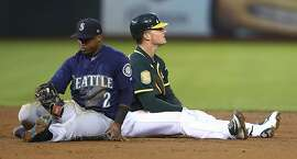 Seattle Mariners' Jean Segura (2) sits beside Oakland Athletics' Matt Chapman after Chapman beat Segura's tag into second base with a double in the third inning of a baseball game Monday, Aug. 13, 2018, in Oakland, Calif. (AP Photo/Ben Margot)
