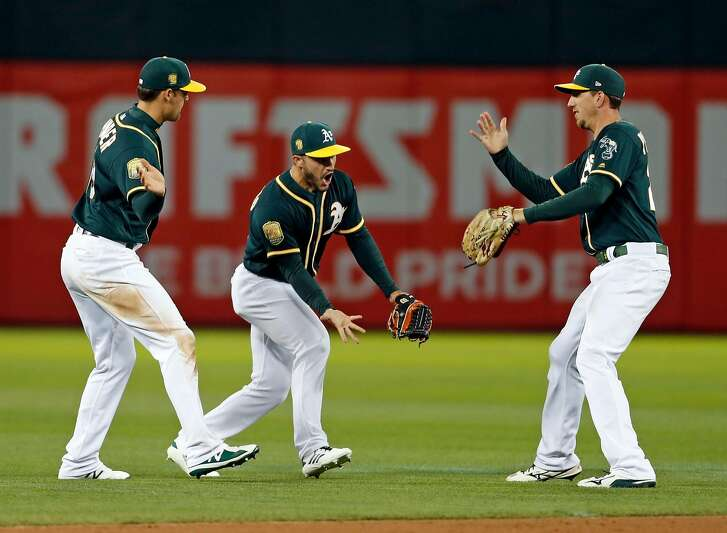 Oakland Athletics' Chad Pinder, Ramon Laureano and Stephen Piscotty celebrate A's 7-6 win over Seattle Mariners in MLB game at Oakland Coliseum in Oakland, Calif. on Monday, August 13, 2018.