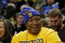 Musician E-40 smiles as he watches an NBA basketball game between the Golden State Warriors and the Minnesota Timberwolves in Oakland, Calif., Saturday, Dec. 27, 2014. (AP Photo/Jeff Chiu)