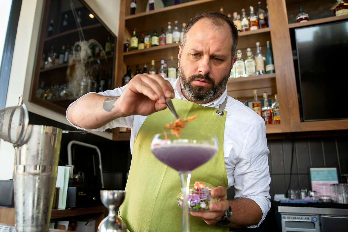 Lead bartender Patrick Poelvoorde finishes off making a Violet Skies drink by placing edible flowers on top at Violet's Tavern in San Francisco, Calif. on Friday, August 10, 2018.